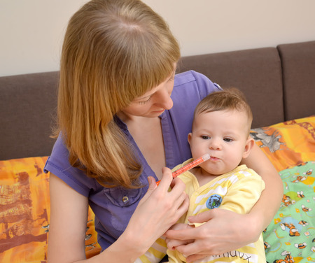 2 5 months: The woman gives to the sick baby medicine by means of the batcher. Treatment