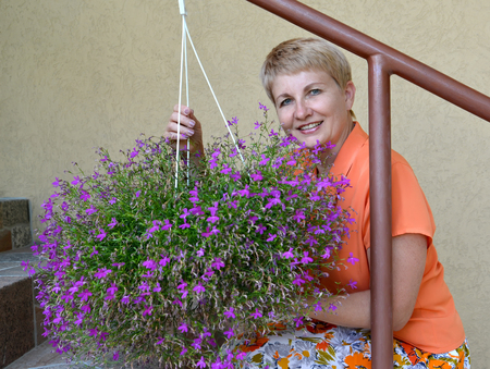 50 to 55 years: The joyful woman of average years sits on a ladder and supports a cache-pot with decorative flowers a lobelia
