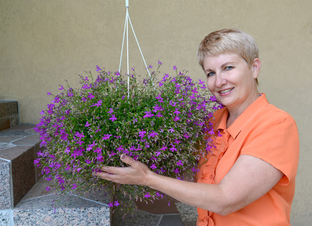 50 to 55 years: The joyful woman of average years supports a cache-pot with decorative flowers a lobelia