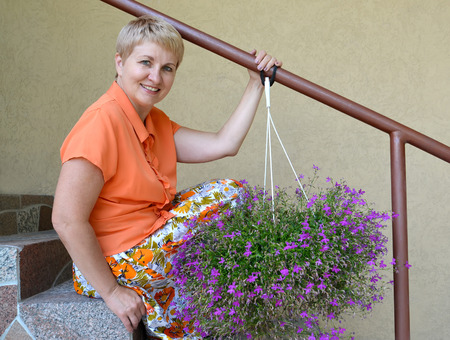 50 to 55 years: The joyful woman of average years sits on a ladder with decorative flowers a lobelia