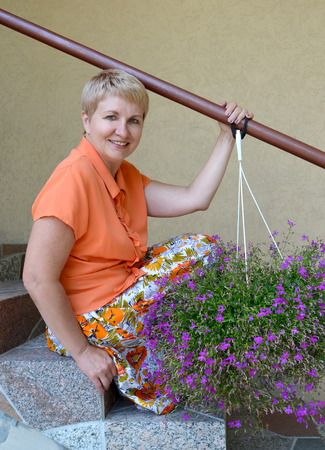 The joyful woman of average years sits on a ladder with decorative flowers a lobelia