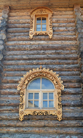 without windows: Two windows with wooden carved platbands on a timbered wall