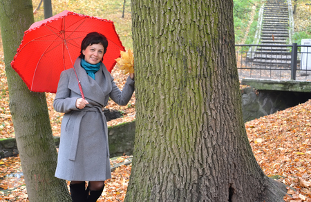 age 35 40 years: The woman of average years costs under a red umbrella in autumn park Stock Photo