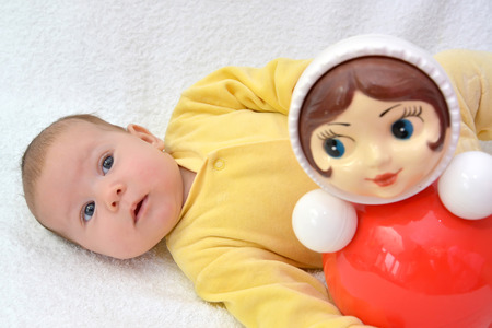 1 2 month: The two-month baby lies near a doll tumbler toy on a white background