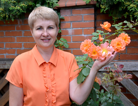 The cheerful woman of average years shows a rose hand in a garden Stock Photo