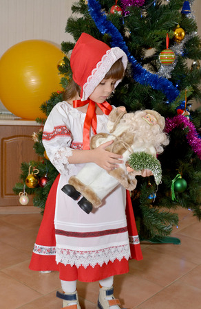 new ages: The little girl in a suit of the Little Red Riding Hood with toy Santa Claus on hands stands near a New Year tree