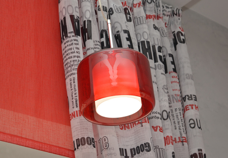 plafond: The lamp with a red plafond against a portiere and rolshtor Stock Photo