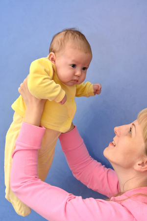 age 30 35 years: The young woman lifts on the babys hands