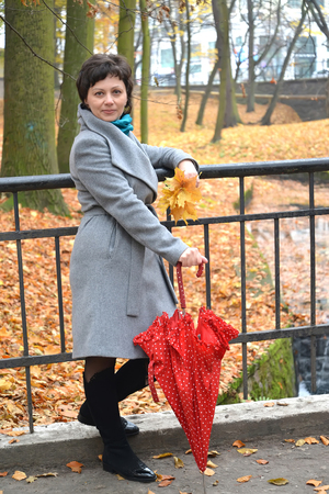 age 35 40 years: The woman of average years keeps a red umbrella in autumn park