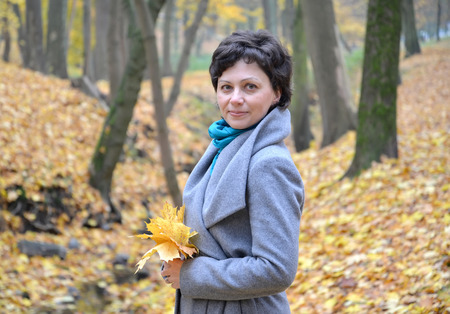 Portrait of the woman of average years with yellow maple leaves in hands. Autumn wood