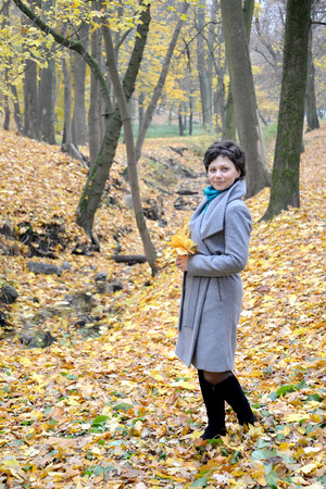 average woman: The woman of average years costs with yellow maple leaves in hands. Autumn park