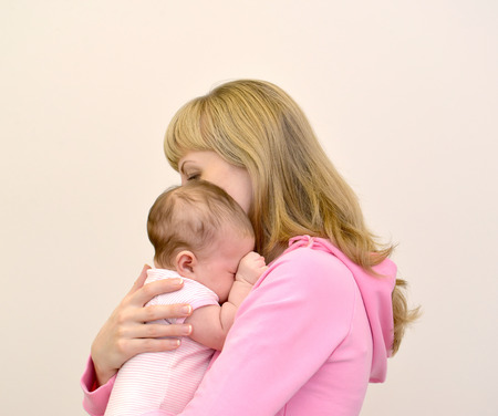 baby crying: The young woman embraces the crying baby Stock Photo
