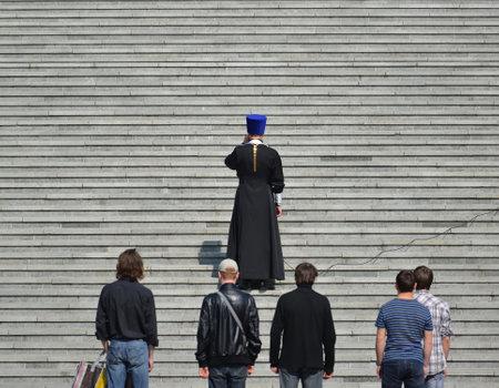 sotana: Kaliningrado, Rusia - 11 de abril, 2015: El sacerdote ortodoxo dice una oración en los pasos de la catedral de Cristo Salvador en Kaliningrado