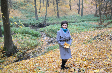 average woman: The woman of average years against a stream in the autumn wood