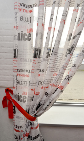 without windows: Curtain from newspaper fabric with red pickup