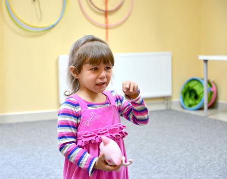 cries: The little girl cries in kindergarten