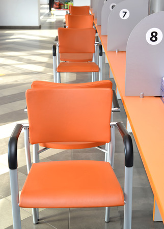 collective: Orange chairs about a collective desktop. Hall of customer service
