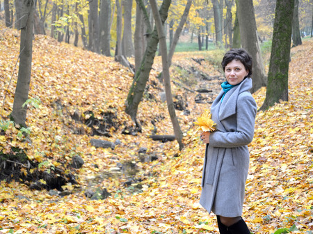 average woman: The woman of average years costs with yellow maple leaves in hands. Autumn wood Stock Photo