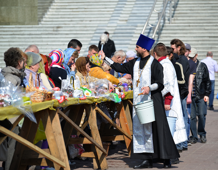 believers: KALININGRAD, RUSSIA - APRIL 11, 2015: The orthodox priest consecrates believers and Easter cakes for Easter