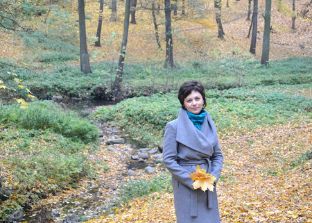 age 35 40 years: The woman of average years stands near a stream in autumn park