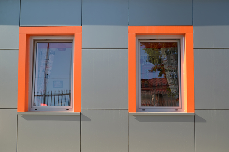 Two windows with orange frames on a gray wall of the building