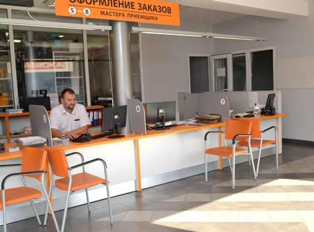 color consultant: KALININGRAD, RUSSIA - OCTOBER 03, 2015: The service advisor on a workplace in a hall of customer service. Shop of an autotechnical center