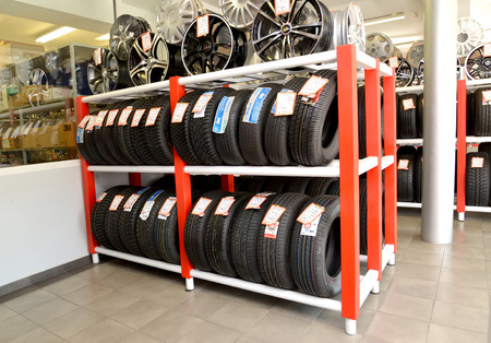 trading floor: KALININGRAD, RUSSIA - OCTOBER 03. 2015: A rack with tires and rims in a trading floor. Shop of an autotechnical center Editorial