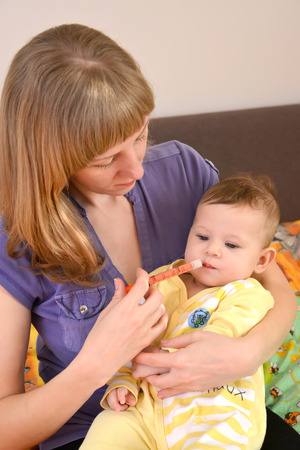 gives: Mother gives to the sick baby medicine by means of the batcher. Treatment Stock Photo