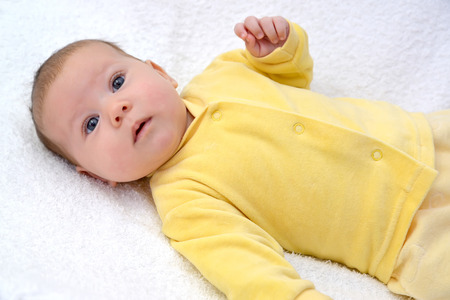 1 2 month: The baby lies on a back on a white background