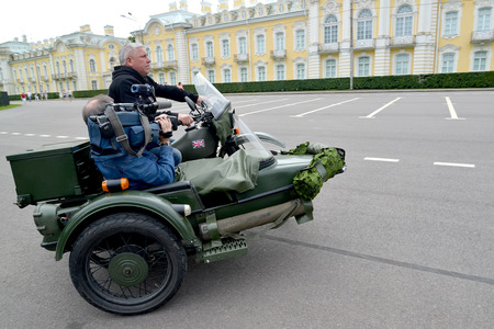 sidecar: PETERHOF, RUSSIA - JULY 26, 2015: The driver and the video operator go on an old military English motorcycle with sidecar