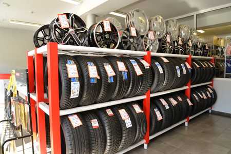 trading floor: KALININGRAD, RUSSIA - OCTOBER 03, 2015: A rack with tires and rims in a trading floor. Shop of an autotechnical center Editorial