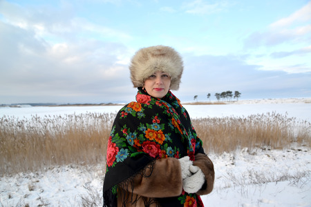 average woman: The woman of average years in a fur cap and a colorful shawl costs on the bank of the winter lake