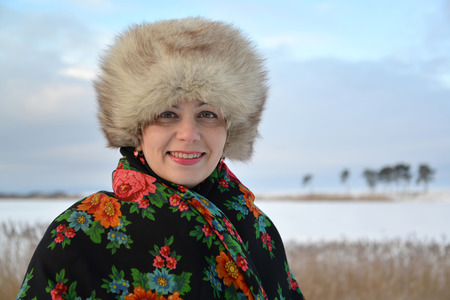 average woman: Portrait of the woman of average years in a fur cap and a colorful shawl against the winter lake Stock Photo