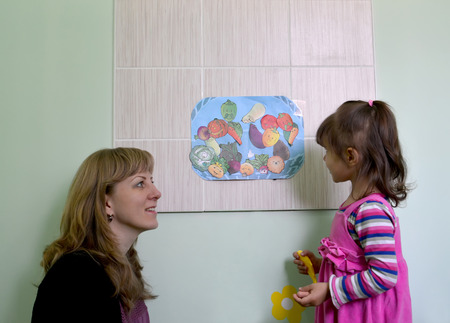 considers: The little girl with mother considers drawings of vegetables in studio of creative development