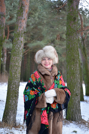 average woman: Portrait of the cheerful woman of average years in the winter pine wood