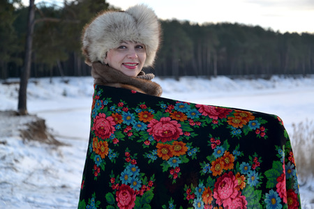age 35 40 years: The woman in a pavlovo-posadsky scarf costs on the bank of the lake. Winter landscape Stock Photo