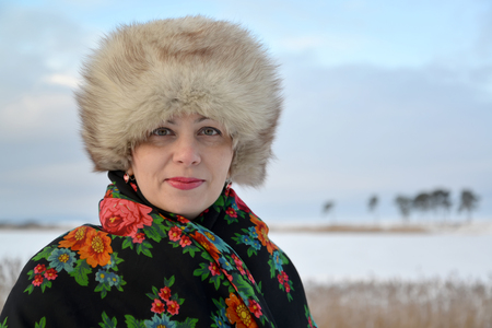 age 35 40 years: Portrait of the woman of average years in a fur cap and a colorful shawl against the winter lake Stock Photo