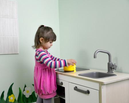 plays: The little girl plays in childrens kitchen. Kindergarten Stock Photo