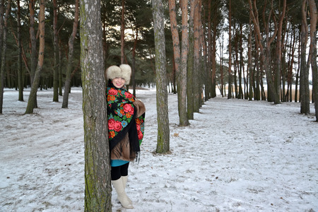 average woman: The woman of average years costs in the young pine wood. Winter landscape