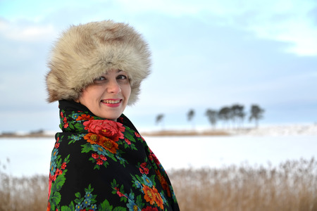 age 35 40 years: The womans portrait half-turned in a fur cap and a colorful shawl against the winter lake