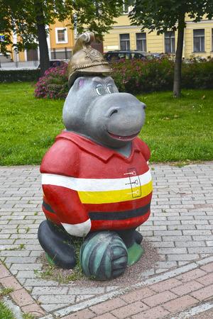 fire helmet: ST. PETERSBURG, RUSSIA - JULY 23, 2015: Hippopotamus in an old fire helmet, a garden sculpture Stock Photo
