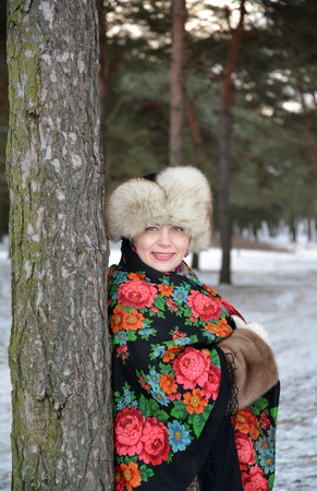 average woman: Portrait of the joyful woman of average years in the winter pine wood Stock Photo