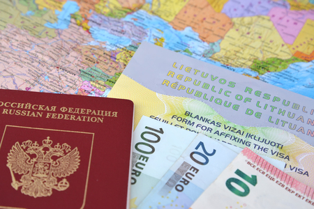 simplified: The Russian international passport, euro and the Lithuanian simplified transit document by rail (UPD ZhD) lie on the political map Stock Photo