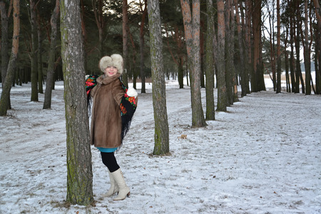 average woman: The woman of average years in a fur coat costs in the young pine wood