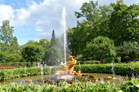 breaking off: PETERHOF, RUSSIA - JULY 24, 2015: The Triton Who Is Breaking Off a Mouth to a Sea Monster fountain (Hothouse) in Nizhny park