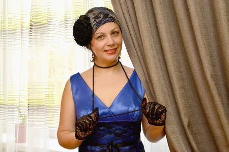 a beads: The woman of average years in a hat with a veil holds a beads in hand