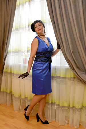 average woman: The coquettish woman of average years in a blue dress is by the window