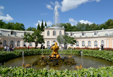 breaking off: PETERHOF, RUSSIA - JULY 24, 2015: The Triton Who Is Breaking Off a Mouth to a Sea Monster fountain against the Big greenhouse in Nizhny park