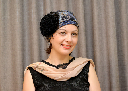 average woman: The joyful woman of average years in a hat with a veil and a scarf. Portrait