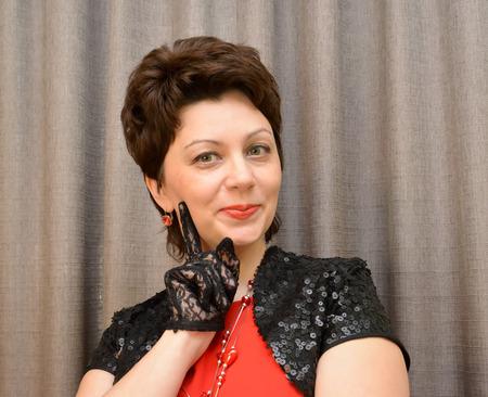 bolero: The coquettish woman of average years in black openwork gloves and a bolero. Portrait
